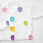 beyaz örülmüş çiçek süslemeli bebek hırkası örnek